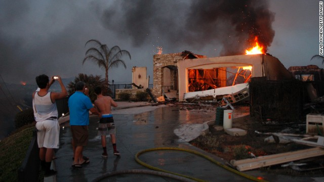 Residents photograph the burning ruins of their home that was destroyed in a wildfire in Carlsbad, California, on May 14. Drought conditions have fueled several wildfires across the state, fire officials said.