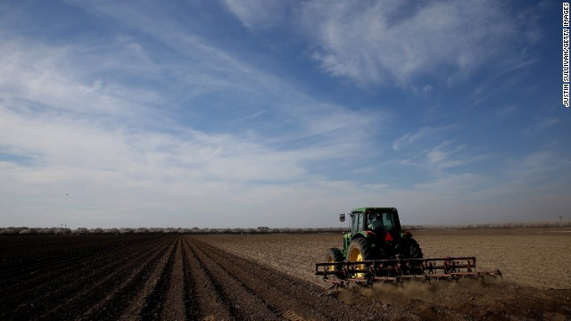 A tractor plows a field in Firebaugh, California, on February 25. Almond farmer Barry Baker had 1,000 acres -- 20% -- of his almond trees removed because he didn't have access to enough water to keep them alive.