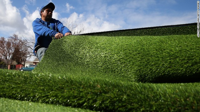 A worker installs an artificial lawn in front of an apartment building in San Jose, California, on January 30.