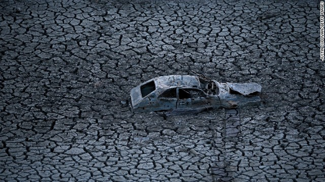 A car sits in the dried and cracked earth at the bottom of the Almaden Reservoir in San Jose, California, on January 28.