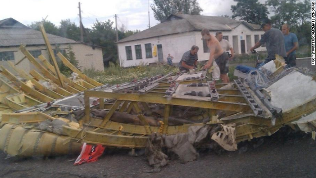 People inspect a piece of wreckage believed to be from Malaysia Airlines Flight 17 in Ukraine. This image was posted to Twitter.