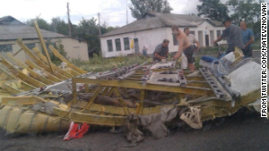 People inspect wreckage thought to be from Malaysia Airlines Flight 17 in Ukraine. This image was posted to Twitter.