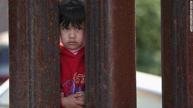 A child on the Mexican side of the U.S.-Mexico border fence looks into Arizona.