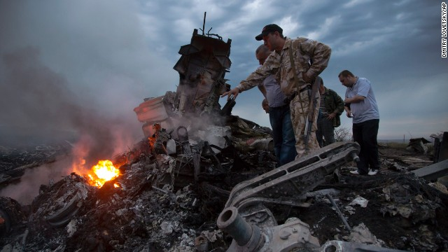 People inspect the crash site on Thursday, July 17.