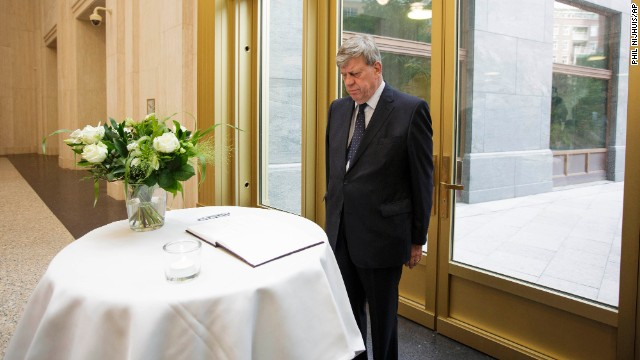 Dutch Justice Minister Ivo Opstelten observes a moment of silence after signing a condolence book in The Hague, Netherlands, on July 18.