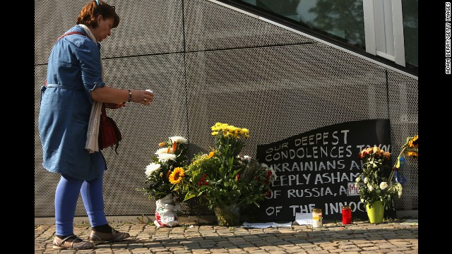 A Berlin woman places a candle at a memorial for the victims on July 18.