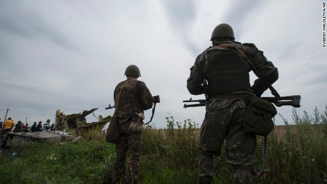 Pro-Russian fighters stand guard as the Organization for Security and Co-operation in Europe delegation arrives at the crash site of Malaysia Airlines Flight 17 in eastern Ukraine on Friday, July 18.