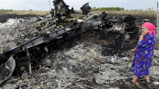 A woman looks at wreckage at the Malaysia Airlines Flight 17 crash site on July 19.
