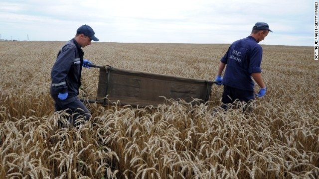 Ukrainian rescue workers walk through a wheat field with a stretcher as they collect the bodies of victims on July 19.