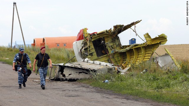 Armed rebels walk past large pieces of the Boeing 777 on July 19.