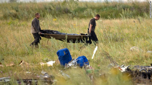 Emergency workers carry the body of a victim at the crash site of Malaysia Airlines Flight 17 in eastern Ukraine on Saturday, July 19.