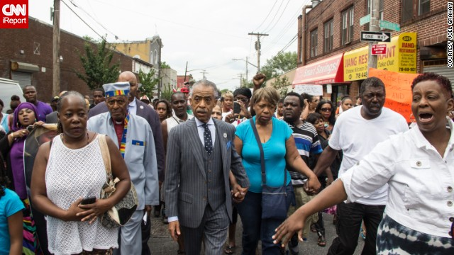 People participate in a demonstration against the death of Eric Garner after he was taken into police custody in Staten Island.<a href='http://ireport.cnn.com/docs/DOC-1153998'> Joel Graham</a> photographed the July 2014 demonstration, and captured this image of Garner's friends and family rallying alongside the Rev. Al Sharpton.