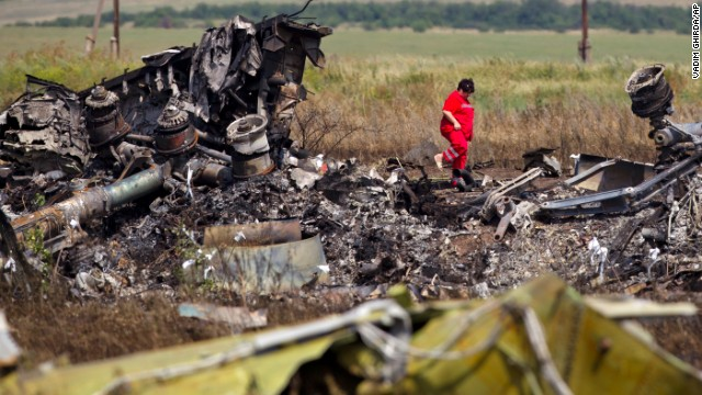A woman walks among charred debris at the crash site on July 20.