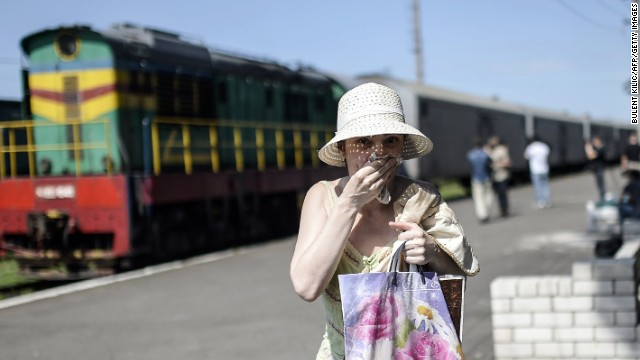 A woman covers her mouth with a piece of fabric July 20 to ward off smells from railway cars that reportedly contain passengers' bodies.
