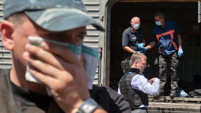 A man covers his face with a rag as members of the Organization for Security and Co-operation in Europe and the Dutch National Forensic Investigations Team inspect bodies in a refrigerated train near the crash site in eastern Ukraine on July 21. The remains of 16 people are still missing, Ukrainian President Petro Poroshenko said.
