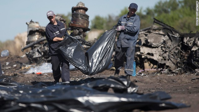 Emergency workers carry a victim's body in a bag at the crash site on July 21. Search teams have recovered more than 270 bodies, officials say.