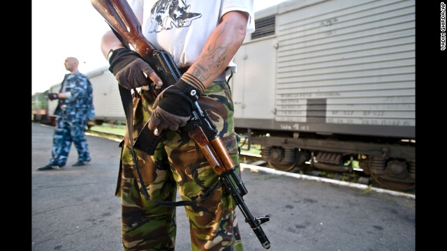 An armed pro-Russian rebel stands guard next to a refrigerated train loaded with bodies in Torez, Ukraine, on Sunday, July 20.
