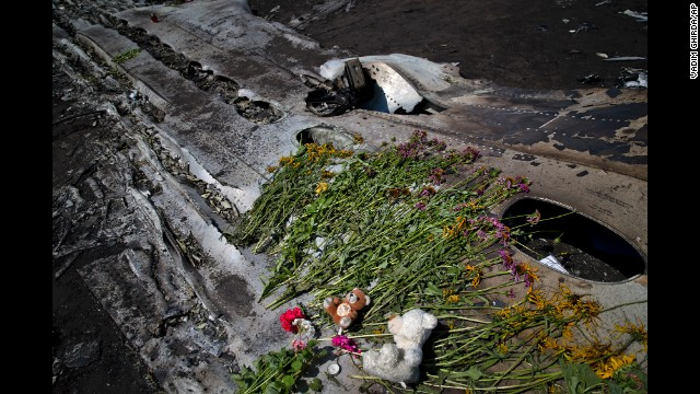 Toys and flowers sit on the charred fuselage of the jet as a memorial on July 20.