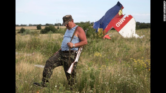 A pro-Russia rebel passes wreckage from the crashed jet near the eastern Ukraine village of Hrabove on Monday, July 21.