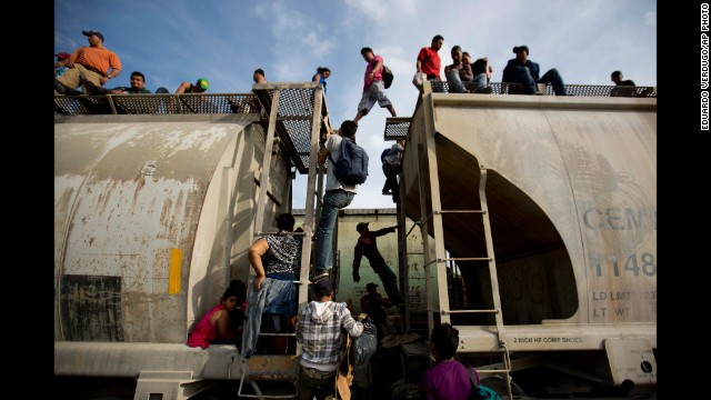 Central American migrants climb on a northbound train during their journey