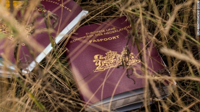 Two Dutch passports belonging to passengers aboard Malaysia Airlines Flight 17 lie in a field at the site of the crash on Tuesday, July 22. The passenger plane was shot down last week above Ukraine. All 298 people aboard were killed, and much of what they left behind was scattered in a vast field of debris.