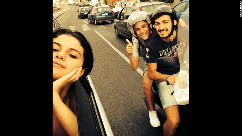 "Actress and singer Selena Gomez poked her head out of her vehicle to take a selfie with two fans in Italy on Friday, July 18. The photo was posted <a href='http://instagram.com/p/qmYk8FujGq/' target='_blank'>on her Instagram account</a> with the message: ""I told them I would :)"""