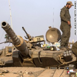 Israeli soldiers carry a shell as they prepare their Merkava tanks stationed at an army deployment along the Israeli Gaza border, on July 22, 2014.
