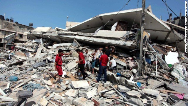 Palestinians inspect destroyed buildings and collect usable items after an Israeli air assault on July 22.