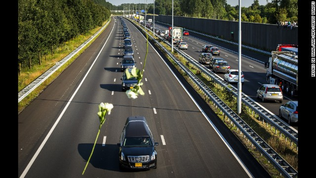 Flowers are thrown from a bridge Wednesday, July 23, as hearses carry victims to Hilversum.