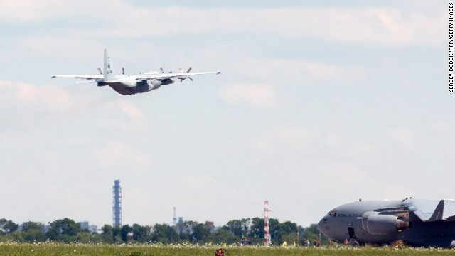 The Hercules carrying the bodies takes off from Kharkiv airport, as a C17 aircraft from the Royal Australian Air Force taxis.