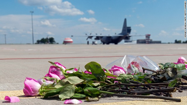 Flowers lie on the tarmac as a Hercules transport aircraft of the Royal Dutch Air Force prepares to take off from Kharkiv airport.