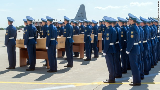 Ukrainian soldiers stand next to coffins carrying the remains of the victims during a ceremony at Kharkiv airport.