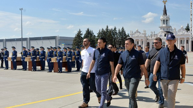 International experts march towards a plane at Kharkiv airport to accompany the remains of victims to the Netherlands.