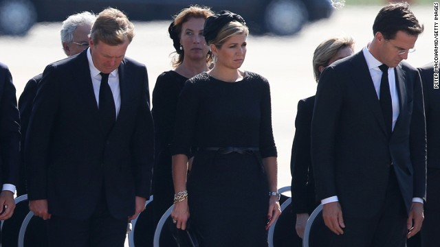 Dutch King Willem-Alexander, Queen Maxima and Prime Minister Mark Rutte stand together as unidentified bodies are transferred to hearses.