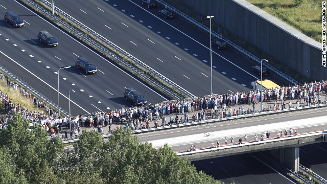 This aerial photo shows people watching from a bridge as a convoy of hearses makes its way from Eindhoven air base to Hilversum.