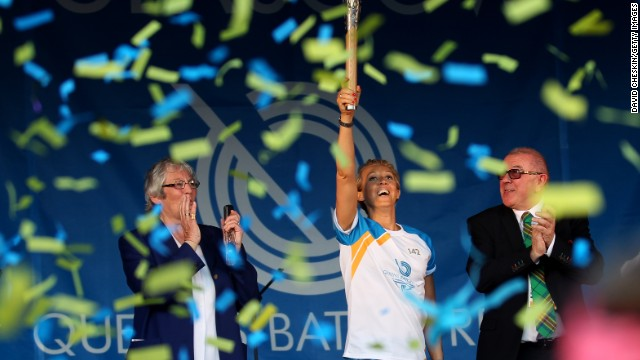Athlete Allison Curbishley holds aloft the Queen's Baton after its arrival in Glasgow after being transported around 70 nations in a relay.