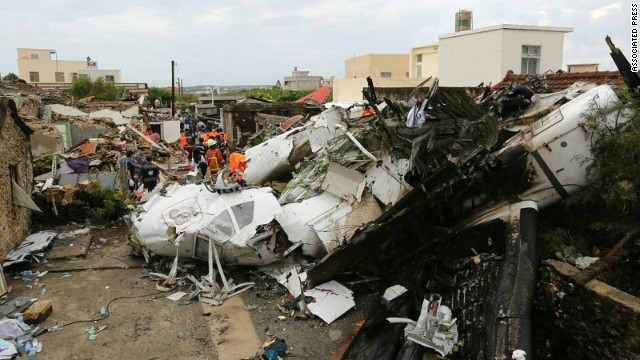 Rescue workers survey the wreckage of TransAsia Airways Flight GE222 on the Taiwanese island of Penghu on Thursday, July 24. The plane was attempting to land in stormy weather but crashed on the island late Wednesday, killing more than 40 people and wrecking houses and cars on the ground.
