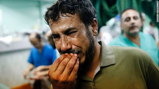"A Palestinian man cries after bringing a child to the Kamal Adwan hospital in Beit Lahiya on Thursday, July 24. The child was wounded in <a href='http://www.cnn.com/2014/07/24/world/meast/mideast-crisis/index.html'>a strike on a school</a> that was serving as a shelter for families in Gaza. It's unclear who was behind the strike. The Israeli military said it was ""reviewing"" the incident, telling CNN that a rocket fired from Gaza could have been responsible."