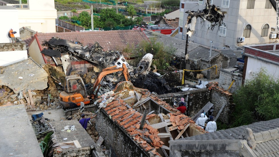 Rescue workers and firefighters search through the wreckage of TransAsia Airways flight GE222 on Thursday, July 24, after it crashed near the airport at Magong on the Penghu island chain a day before. The domestic TransAsia Airways flight was carrying 54 passengers and four crew members when it crashed in the Penghu island chain. There were 10 survivors.