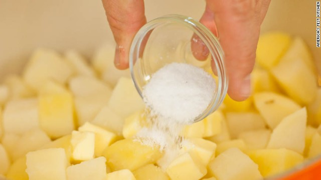5. Add 3 tablespoons unsalted butter, cut into 12 pieces, 1 1/2 teaspoons kosher salt, and pinch cayenne pepper. Mix with rubber spatula until potatoes are coated with thick, starchy paste, about 30 seconds.
