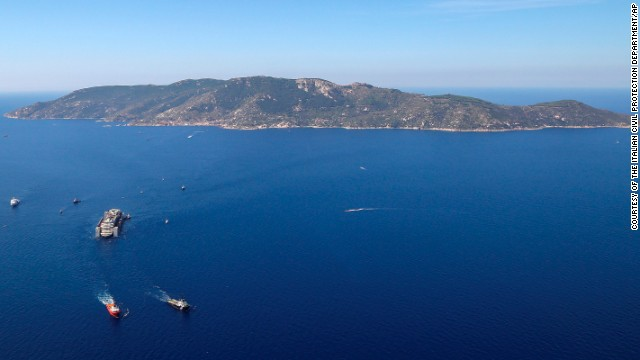 Tugboats tow the wreck of the Costa Concordia as it leaves Italy's Giglio Island on Wednesday, July 23. Two and a half years after running aground, the Costa Concordia cruise ship is being to be towed north to the Italian port at Genoa to be dismantled. Thirty-two people died in the disaster that drew global attention.