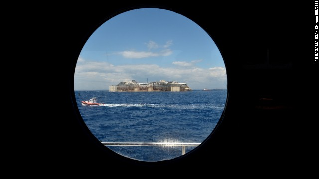 A view from a porthole shows the wreck of the Costa Concordia as it's being towed on July 23. It'll take about two years to dismantle the massive cruise liner.