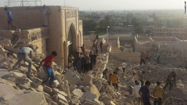 People in Mosul walk on the rubble of the destroyed Mosque of The Prophet Yunus, which is Arabic for Jonah, on Thursday, July 24.