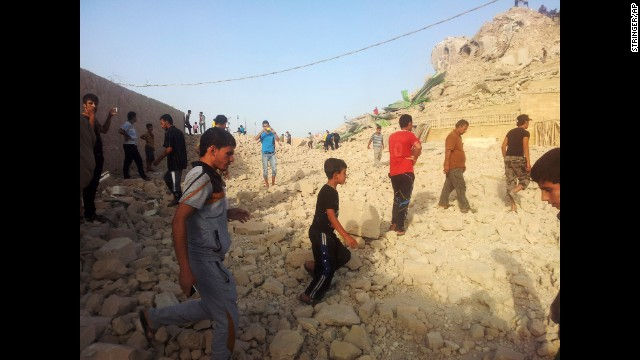Iraqis walk on the rubble of what was once the tomb of the prophet Jonah, who famously survived three days in the belly of a whale.