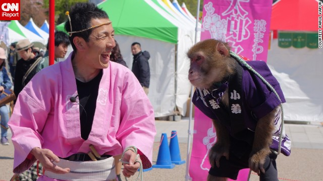 "Parul Kapur came across a man and monkey performing in Ueno Park while searching for cherry blossoms in Tokyo, Japan. Kapur said, ""The joy and enthusiasm on the man's face was exceptionally contagious, bringing a moment of happiness to every adult and kid in the area."""