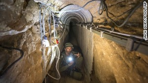 An Israeli army officer shows a tunnel Israel says was used by Palestinian militants for cross-border attacks.