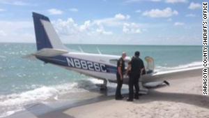 Sarasota County Sheriff\'s Office officials look over a plane that hit a father and daughter Sunday on a Florida beach.