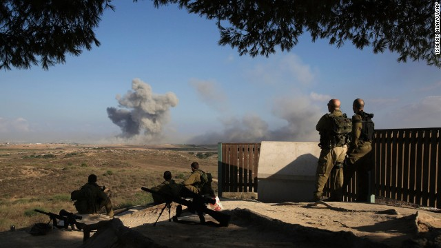 Israeli soldiers watch a bomb explode along the border with Gaza before the 12-hour cease-fire on July 26.