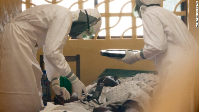 In this photo provided by Samaritan's Purse, Dr. Kent Brantly, left, treats an Ebola patient in Monrovia. On Saturday, July 26, the North Carolina-based group said Brantly tested positive for the disease and was being treated at a hospital in Monrovia.