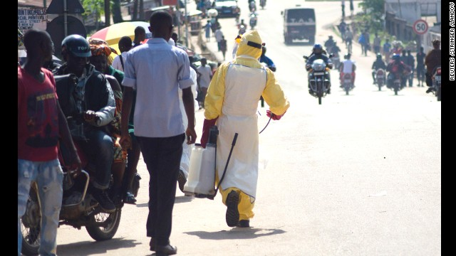 A health worker with disinfectant spray walks down a street outside the government hospital in Kenema, Sierra Leone, on Thursday, July 10.